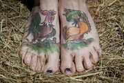 Jenn Cole-Hiatt's tattoos include a rooster flirting with a duck on her feet. The tattoos were based on illustrations from an old postcard.