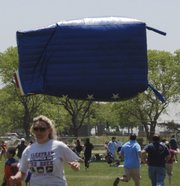 "In this June 4, 2011, photo, participants in an Oceanside, N.Y., soccer tournament run from an airborne inflatable ""bounce house"" after high winds sent it flying, injuring 13 people, one critically. Saturday&squot;s inflatable mishap is the latest in a growing series of similar accidents, experts say."