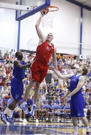Red Team player Cole Aldrich extends for a jam between Blue Team players Tyshawn Taylor, left, and Jordan Juenemann during the alumni scrimmage game on Wednesday, June 8, 2011 at the Horejsi Center.