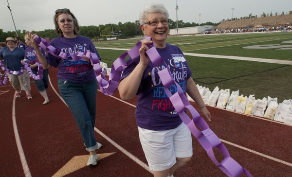 Sharon Wiggins, left, and Glenna Graham walk while holding the survivor chain at the start of Relay For Life of Douglas County in 2011 at Free State High School. This year's event is June 8-9.