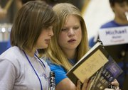 Corrine Yoder-Mulkey, left, and Rachel Opstad look over a book of sheet music during the first rehearsal of the Midwestern Music Academy on Sunday.