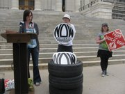Kansas NOW state coordinator Kari Ann Rinker, behind the podium, and the tires in question during June 1 news conference outside the Capitol Building.