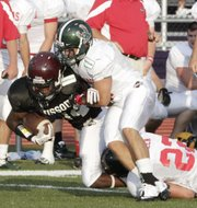 Preston Schenck, Free State, brings down DeVante Bausby in first half action Thursday, June 16, 2011 during the MO-KAN High School All Star football classic at Southwick Stadium Complex in Belton, Missouri.