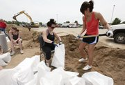 Autumn Bos and Megan Moll fill sand bags along the riverfront Thursday, June 2, 2011, while preparing for the expected flood in Sioux City, Iowa. Gov. Terry Branstad said that all Iowa counties along the Missouri River will be affected by rising water and that residents need to get ready because the worst of the flooding is still upriver.