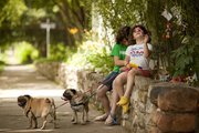 Six-year-old Teagan Hamon, right, and her older sister Tory Hamon, 11, and their two pugs, Fiona, left, and Brutus, stop by the Funkytown garden June 24. The garden sits along the Eighth Street side of Brigid Murphy's home at the corner of Eighth and Indiana streets in Old West Lawrence. Murphy started the garden several years ago and likes that it has become an ever-changing fixture in the neighborhood.