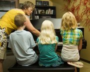 From left, Drew Bond, 11; Olivia Bond, 9; and Taylor Morstorf, 10, watch as piano instructor Karla Grether demonstrates which notes to play during a piano lesson June 23 at her home. Grether uses a teaching method called Simply Music.