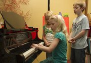 Olivia Bond, 9, practices a song at the piano as Taylor Morstorf, 10 and Drew Bond, 11, sing along  June 23 at piano instructor Karla Grether's home.