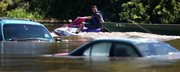 Tim Hogan pulls a jon boat behind his jet ski as he floats past cars owned by Terrible's Casino employees who couldn't move them before flood waters surrounded them Tuesday morning, June 28, 2011, in St. Joseph, Mo. Hogan was going to his rental home on the banks of the river to retrieve what he could from the flooded property.
