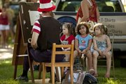 Five-year-old Karma Matchette, center, casts an expression of her own as she waits with Samara Ekstrom, 4, left, and Lilly Woods, 4, while artist John Rasmussen makes a caricature drawing of the three during the Lawrence Originals Party in the Park on Monday at Watson Park. Plenty of Lawrence kids and parents alike spent the afternoon in the park for food, games and entertainment prior to the fireworks show later in the night.