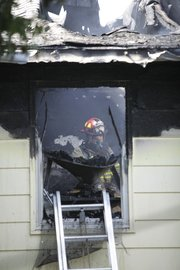 A Lawrence Douglas County Fire & Medical firefighter looks through a damaged window inside a single family home that caught fire about 3:30 p.m. on July 5, 2011. One of the homeowners suffered minor injuries and was taken to Lawrence Memorial Hospital for observation.