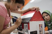 Monica G. Ibrahim, left, and Amany Abdelmeguid, both from Egypt, paint slogans of their country's recent revolution on their dollhouse creation Wednesday, July 6, 2011, at the Nunemaker Center on the Kansas University campus. The dollhouse project is one activity during a KU International Women's leadership seminar. The dollhouses will be donated to the Douglas County CASA playhouse fundraising effort.