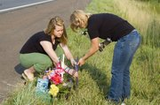 Tonganoxie High School students Sarah Wetta and Rebekah Adcox place a cross on Saturday morning near the crash site of a Thursday rollover accident in which THS student Kylee Wilson, 16, was killed.
