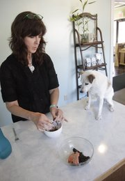 Cathy King, of Kaw Valley Natural Pet Care, feeds her dog Nellie, 10, a natural diet of beet greens and salmon that to keep her healthy. Some pet owners have turned to homemade foods to keep their animal companions healthy.