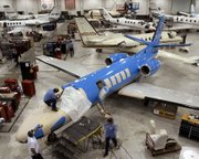 In this Nov. 4, 2004, file photo, workers service Cessna Citation business jets at Cessna's service center in Wichita.