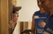 Tal Shavit, Lexington, Mass., pushes her head between a couple of wall studs as she jokes with friends working on the other side during a Bike and Build work day, Wednesday, July 13, 2011 at 214 Comfort Lane in North Lawrence. The volunteers, who are traveling across the country assisting at various build sites, began their journey in Providence, R.I., on June 9 and will end in mid August at Half Moon Bay, Calif.