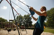 Laura Webb, a personal trainer at Kansas University's student recreation center, demonstrates pulls on a swing at Watson Park.