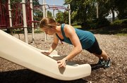 Personal trainer Laura Webb does pushups on a playground slide.