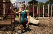 Personal trainer Laura Webb uses the slide on a jungle gym to do split-squat lunges.