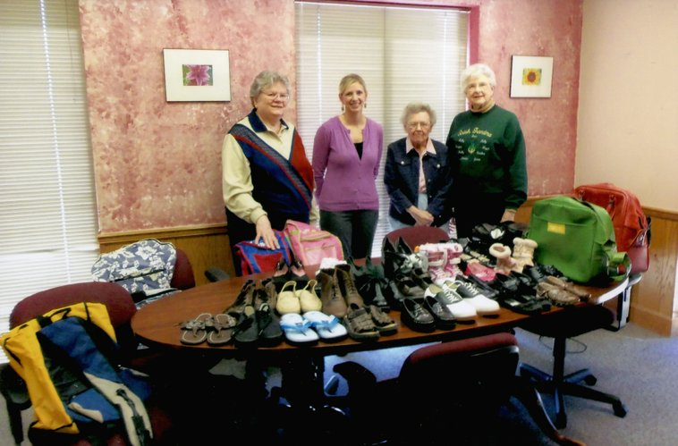 Members of the Omicron Chapter of Delta Kappa Gamma have been collecting shoes and small suitcases for children at KVC Behavioral Health Care Agency in Lawrence. So far, the members have donated at total of 22 small suitcases and 70 pairs of shoes. The most recent delivery, in March, included 30 pairs of shoes and 11 suitcases. From left are Cathey Parsons, Omicron president; Dusti Powell, then-KVC community resource specialist; and Mary Gauthier and Jean O'Toole, both Omicron members, all of Lawrence.
