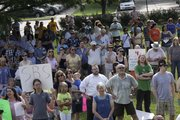 Hundreds of people showed up in South Park on Saturday, July 16, 2011, to rally against the closing of the Social and Rehabilitation Services office in Lawrence.