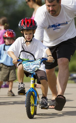 Four-year-old Parker Moore concentrates on balancing without training wheels as his father, Jim, lets go of his bicycle as the two participated in the first annual Community Bike Ride hosted by the Lawrence Central Rotary Club Saturday, July 16, 2011 at the Rotary Arboretum near the YSI sports complex in west Lawrence.