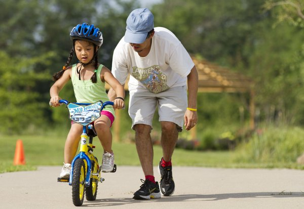 Eight-year-old Ryleigh Leon learns how to ride without training wheels with a little help from Lawrence resident Steve Harrington. He was using a technique to teach riding without wheels that involves letting the children coast down a slight hill so that the kids can focus solely on balancing and not have to worry about pedaling.
