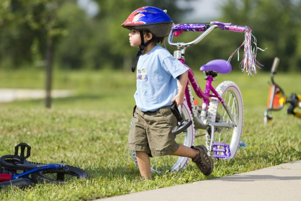 Three-year-old Ida Harrington carries her training wheels to the side of the sidewalk after having them removed from her bicycle during the first Community Bike Ride.