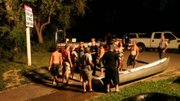 Law enforcement officers speak with a group of people who were on a float trip down the Kansas River on Sunday evening. The group was made up of mostly teenagers who had little or no contact with their parents, who then became concerned. Rescue teams searched for the group and there were no injuries.