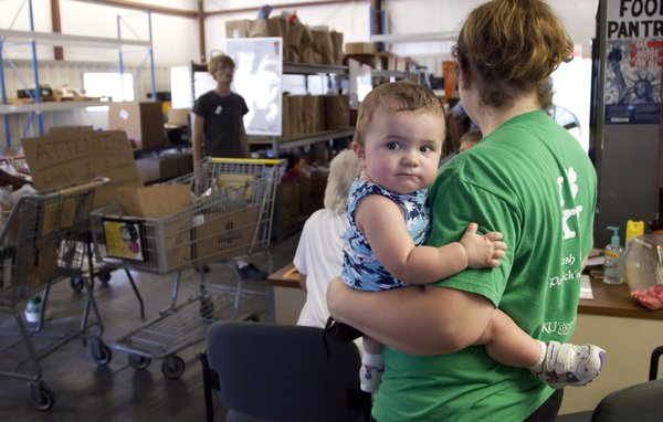 11-month-old Savannah Bennett, hangs on to her mother, Carrie Bennett, as she waits in line for an application at Just Food Tuesday, July 19, 2011.