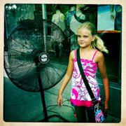 Kaylee West, 9, Shawnee, takes a break in front of a fan while shopping with her grandmother during the annual Lawrence Sidewalk Sale, Thursday, July 21, 2011.