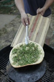 A simple pizza with basil and olive oil can be cooked on a pizza stone laid onto of a Weber grill for an extra smoky flavor.