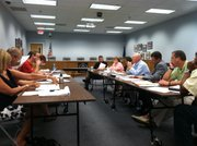 Negotiators for the Lawrence Education Association, seated at the table at left, and representatives for the Lawrence school district, seated at the table at right, go through potential language for the 2011-12 master agreement, which would govern compensation and working conditions for 926 licensed educators in the district. This session was July 21, 2011, at district headquarters, 110 McDonald Drive.