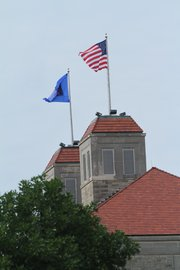 The American flag is displayed all over KU's campus, including this flag flying prominently from the roof of Fraser Hall.