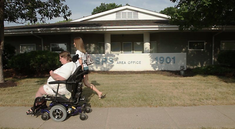 Darlene Mortell, 54, visits the Lawrence SRS office on Thursday, July 28, 2011, to drop off some paperwork that's required for Vocational Rehabilitation services. She is accompanied by Sarah Anderson, her personal care attendant. Mortell uses an electronic wheelchair to get around town, so she's not sure how she will access SRS services when the Lawrence office closes. She can't take her wheelchair to Topeka or Kansas City.
