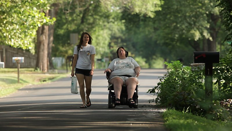 Sarah Anderson, a personal care attendant, walks alongside Darlene Mortell, 54, on Thursday, July 28, 2011, on Learnard Ave. They were on their way to the Kansas Department of Social and Rehabilitation Services office in Lawrence to drop off paperwork. Mortell, who has muscular dystrophy among other health issues, uses SRS for vocational rehabilitation services, and food and medical assistance. She visits the office several times a month.