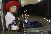 Halley Flory, 6, rests in the back of a horse trailer to admire the grand champion trophy she won in her age group at the horse show at the Douglas County Fair Sunday, July 31, 2011.