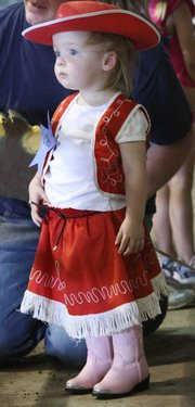 Dressed in her cowgirl outfit, Cleo Trigg, 2, Lawrence, waited for the stick-horse competition on Sunday.