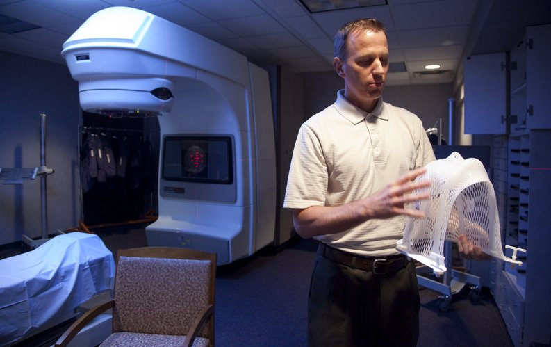 Dr. Darren Klish, a radiation oncologist at Lawrence Cancer Center, displays a mask used for stabilizing a patient during a stereotactic body radiation therapy treatment on Monday, Aug. 1, 2011. Klish explained that the SBRT treatment is very precise in targeting tumors. Behind Klish is the center's accelerator, which is currently being replaced with a newer one.