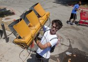Grayson Warrior, Kansas University senior, Lawrence, and staff at The Reserve, 2511 W. 31st St., loads a broken stoplight into a trash bin Monday, Aug. 1, 2011. He and other staffers, in the triple-digit heat, were cleaning up the piles of trash that had overflowed bins in preparation for new renters moving in. The high Monday hit 107, but hottest day ever recorded in Lawrence was 114 on Aug. 10, 1934, the state climatologist said.