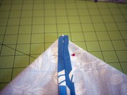 Step 4: At each corner, pull the front and back layers apart so the seams lay flat against each other and match up. It should look like a triangle. Measure 3 inches down from the corner point and mark a line across the triangle. Pin layers together.