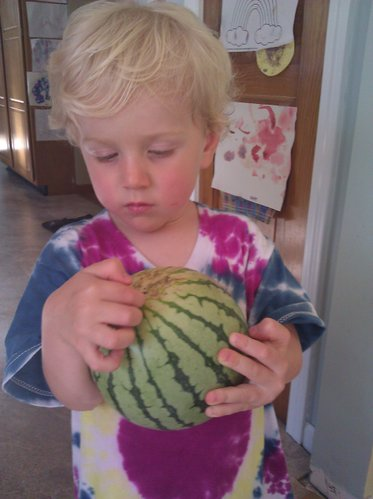 The kiddo with a baby yellow watermelon.