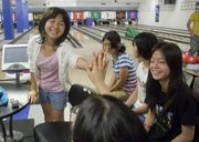 Risa Ito, 15, left, from Hiratsuka, Japan, celebrates a successful score while bowling Wednesday, August 3, 2011, at Jaybowl in the Kansas Union. Students from Hiratsuka, one of Lawrence's sister cities, have been touring the area since July 29 and will return home Sunday. Earlier this year, students from Lawrence toured Japan. In foreground at right is Koharu Suzuki, 14.