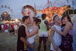 Fair attendees, from left, Jordan Seiger, 16; Shaelyn Marr, 14; and Tyler Ellison and Courtney Curtis, both 16, all of Lawrence, enjoy an evening beneath the carnival lights at Moores' Greater Shows Carnival on Thursday night at the Douglas County Fairgrounds, 2110 Harper St.