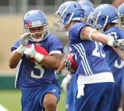 Running back Darrian Miller breaks through a line during the team's first practice on Thursday, Aug. 4, 2011.
