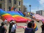 Two large flags are unfurled Saturday at the Capitol during a rally put on by the Kansas Equality Coalition and Kansas National Organization for Women. About 150 people attended.