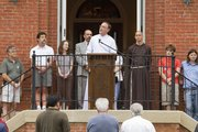 The Rev. Peter Luckey speaks to a crowd from the front entrance of Plymouth Congregational Church, 925 Vt., during an interfaith prayer vigil on Saturday to lament the closing of the Lawrence office of Social and Rehabilitation Services.