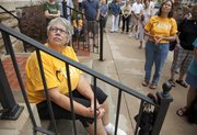 Pennie Von Achen, left, Eudora, sits on the front steps to listen Saturday, Aug. 6, 2011, during an interfaith prayer vigil at Plymouth Congregational Church, 925 Vt., to lament the closing of the Lawrence office of Social and Rehabilitation Services.