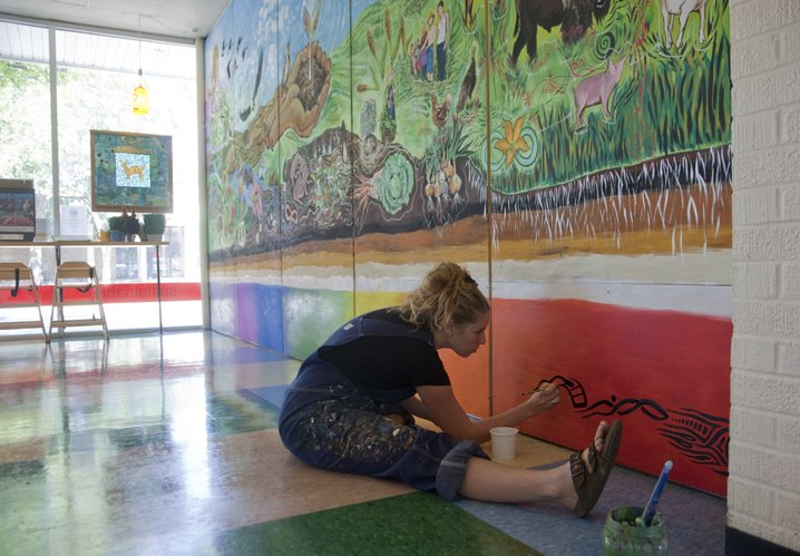 Local artist Heather Reynolds works to complete a large mural on the north interior wall at Local Burger, 714 Vt. The mural focuses on how all plants, animals and humans are connected and important to the sustainability of our planet.