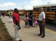 Myrone Grady, school resource officer, and Lynn Harrod, assistant principal, monitor students as they head to buses in the parking lot at South Middle School.