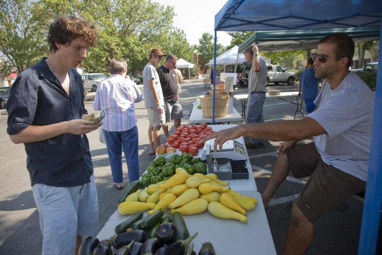 Logan Luce, a Kansas University graduate student, picks up some fresh vegetables from Nathan Atchison, of Atchison Farms, at the Lawrence Farmers' Market on Tuesday, Aug. 16, 2011.